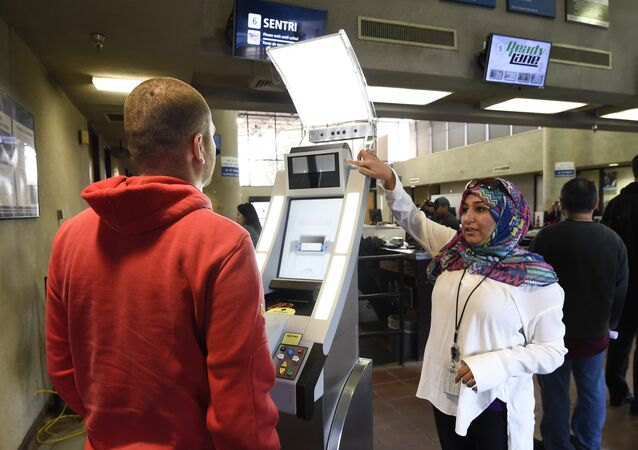 Contractor Sabira Dewji, right, helps a pedestrian crossing from Mexico into the United States at the Otay Mesa Port of Entry have his facial features and eyes scanned at a biometric kiosk Thursday, Dec. 10, 2015, in San Diego