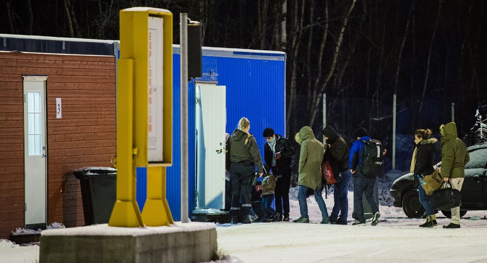 Refugees are welcomed upon arrival at the Norwegian border crossing station at Storskog after crossing the border from Russia on November 11, 2015