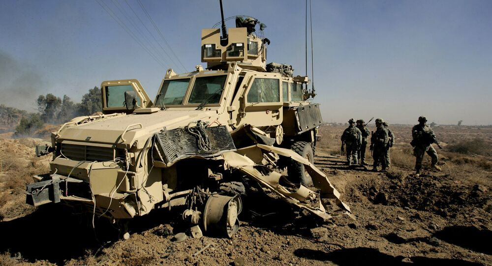 U.S. soldiers secure the area next to a damaged U.S. mine resistant, ambush protected vehicle (MRAP), after a roadside bomb explosion during an operation in the area of Al-leg, some 40 miles south of Baghdad, Iraq (File)