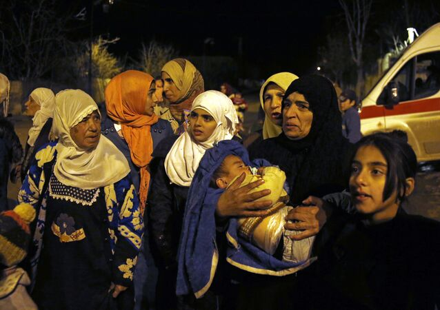 In this Monday, Jan. 11, 2016 photo, people wait to leave the besieged town of Madaya, northwest of Damascus, Syria. Aid convoys reached three besieged villages on Monday — Madaya, near Damascus, where about 400 people need to be evacuated immediately to receive life-saving treatment for medical conditions, malnourishment and starvation, and the Shiite villages of Foua and Kfarya in northern Syria
