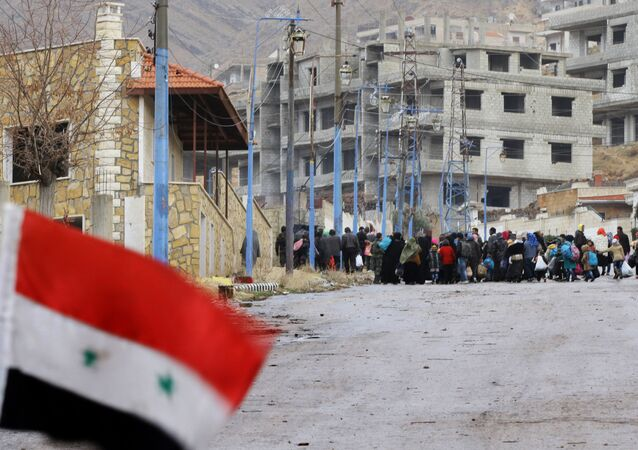 A Syrian national flag flutters on a barricade erected at the entrance of the besieged rebel-held Syrian town of Madaya as residents wait for a convoy of aid from the Syrian Arab Red Crescent on January 14, 2016