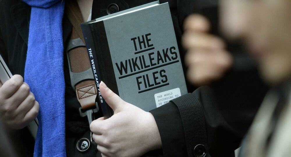 A supporter of WikiLeaks founder julian Assange holds a copy of The WikiLeaks Files outside the Ecuadorian embassy in central London, Britain February 5, 2016