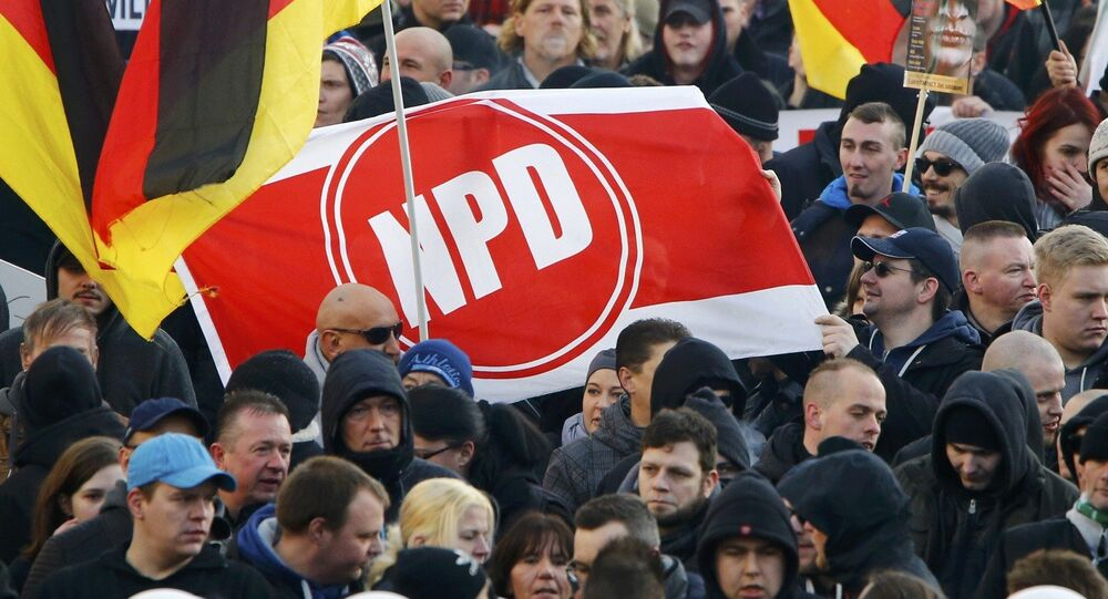 Supporters of anti-immigration right-wing movement PEGIDA (Patriotic Europeans Against the Islamisation of the West) hold up a banner with the logo of the far-right National Democratic Party (NPD) as they take part in in demonstration march, in reaction to mass assaults on women on New Year's Eve, in Cologne, Germany, January 9, 2016.