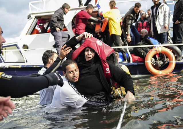 Migrant families - helped by rescuers - disembark on the Greek island of Lesbos after crossing with other migrants and refugees the Aegean Sea from Turkey, on November 25, 2015.