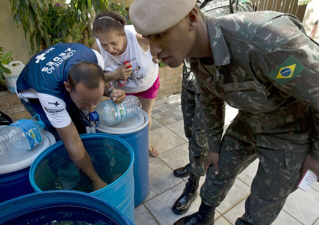 Soldiers and a Health Ministry agent look for larvae of Aedes aegypti mosquito, vector of the Zika, Dengue ans Chikungunya viruses, during an operation to fight them in Sao Paulo, Brazil on February 3, 2016