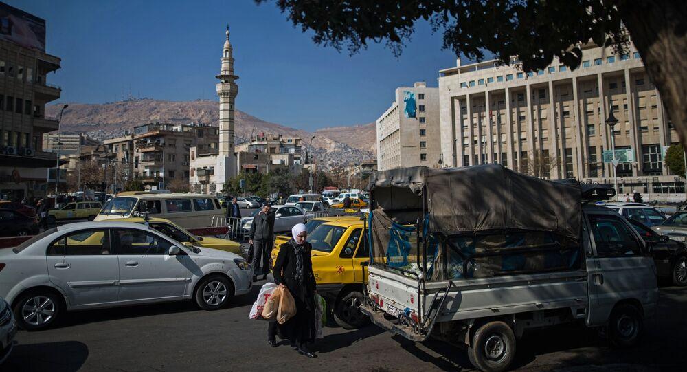 Pedestrians on a street in Damascus.
