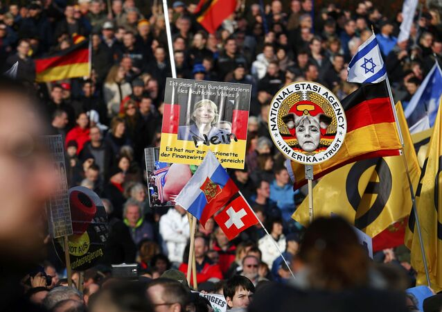 Supporters of the anti-Islam movement Patriotic Europeans Against the Islamisation of the West (PEGIDA) hold posters depicting German Chancellor Angela Merkel during a demonstration in Dresden, Germany