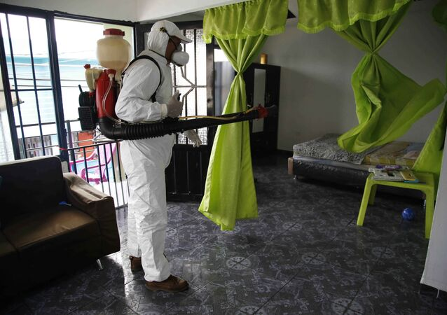 A health worker sprays insecticide inside the home of a woman diagnosed with the Zika virus in Acacias, Colombia