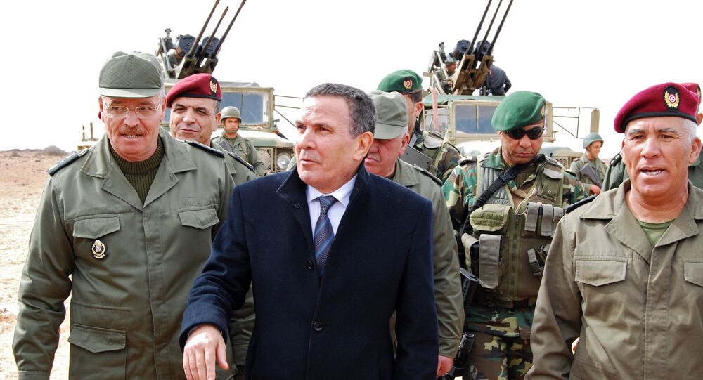 Tunisian Defense minister Farhat Horchani, center, with Chief of Staff of the Army Ismael Fathalli, left, attend a presentation of the anti-jihadi fence, in near Ben Guerdane, eastern Tunisia, close to the border with Libya, Saturday, Feb. 6, 2016.