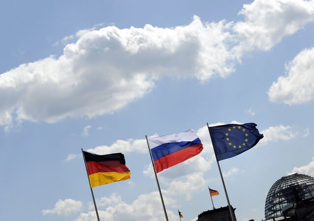 The Russian flag flutters between the flags of Germany (L) and Europe as in the background is seen the cupola of the Reichstag housing the Bundestag at the Chancellery in Berlin