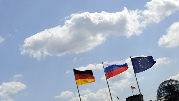 The Russian flag flutters between the flags of Germany (L) and Europe as in the background is seen the cupola of the Reichstag housing the Bundestag at the Chancellery in Berlin - Sputnik International