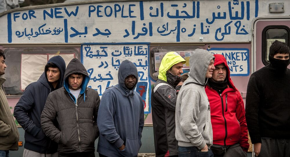 Refugees stand in the so-called Jungle migrant camp in Calais, northern France