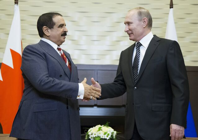 Russian President Vladimir Putin (R) welcomes Bahrain's King Hamad bin Isa Al Khalifa during a meeting at the Bocharov Ruchei state residence in Sochi, Russia