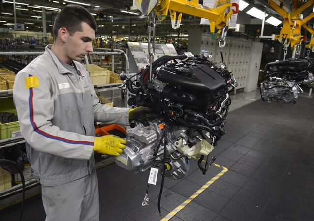 An employee works on the engine assembly line of the Peugeot 208 car by French car maker PSA Peugeot Citroen at the company's automobile factory in Trnava, western Slovakia