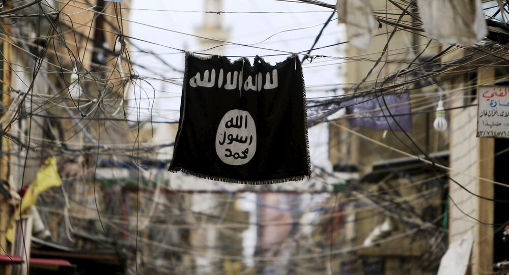 An Islamic State flag hangs amid electric wires over a street.