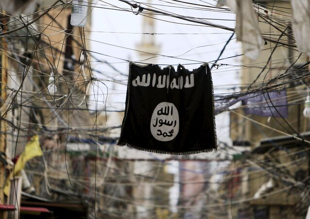A Daesh flag hangs amid electric wires over a street.