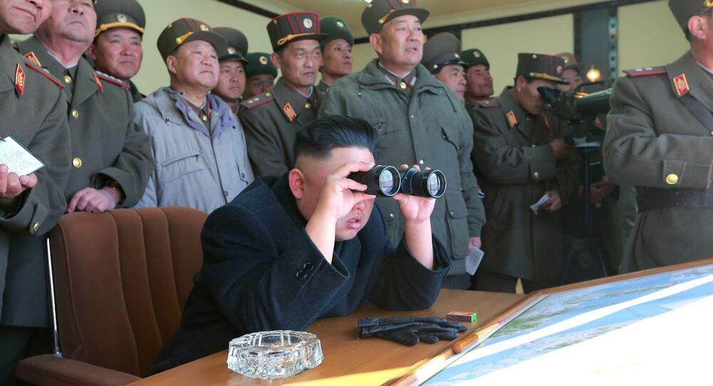 North Korean leader Kim Jong Un uses a pair of binoculars to watch live ammunition firing drills.