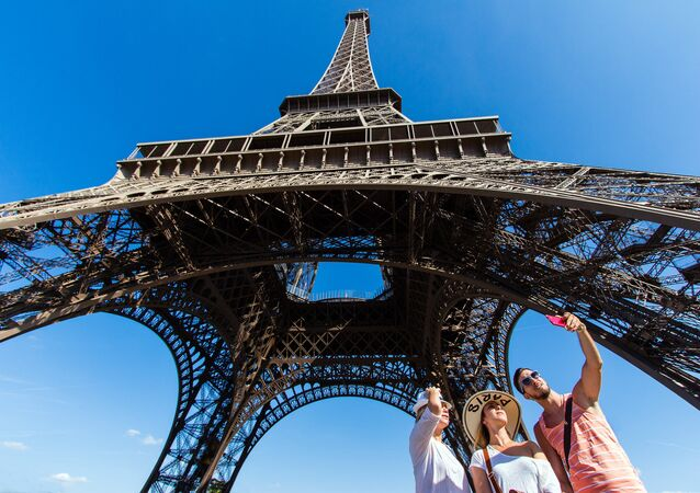 People taking a selfie in front of the Eiffel Tower, Paris.