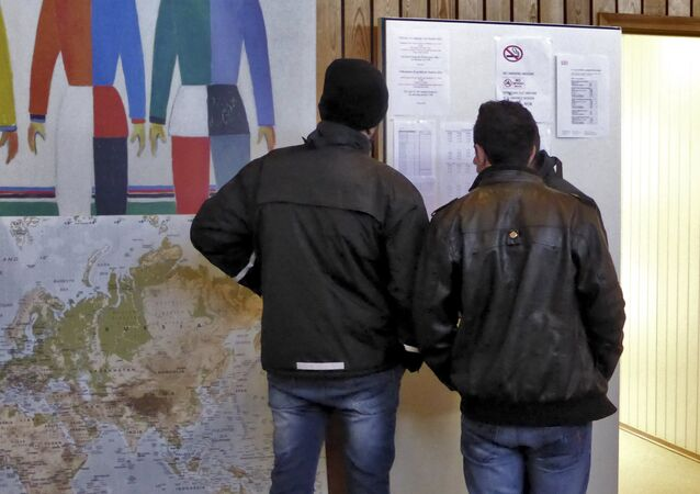 Men look at a notice board at a reception center for Syrian asylum-seekers in Naerboe, Norway, January 19, 2016.