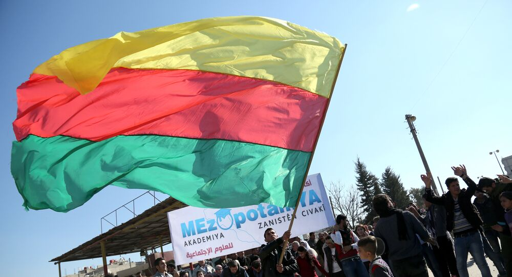 A Kurdish man waves a large flag of the Democratic Union Party (PYD)