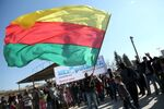 A Kurdish man waves a large flag of the Kurdish People's Protection Units (YPG) political wing, the Democratic Union Party (PYD), during a demonstration against the exclusion of Syrian-Kurds from the Geneva talks in the northeastern Syrian city of Qamishli on February 4, 2016