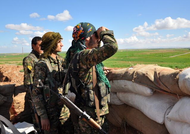 Members of the Kurdish People's Protection Units (YPG) monitor Daesh (ISIS) terrorist positions in the Syrian town of Ras al-Ain, close to the Turkish border on 13 March 2015