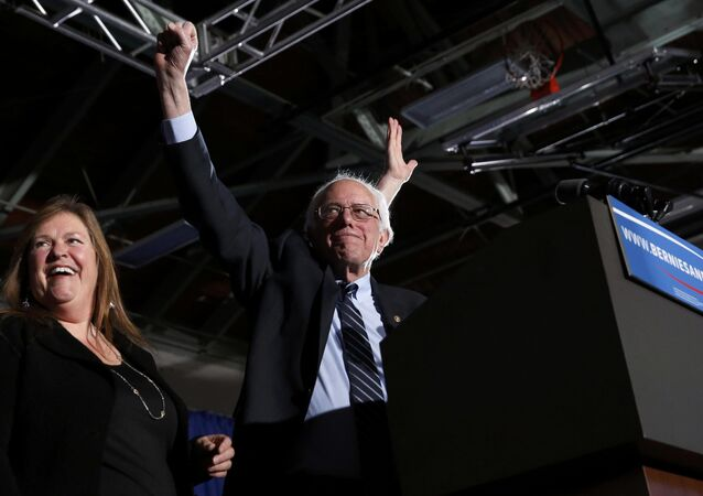 Democratic U.S. presidential candidate Bernie Sanders thrusts his fist in the air as he arrives with his wife Jane at his 2016 New Hampshire presidential primary night victory rally in Concord, New Hampshire February 9, 2016