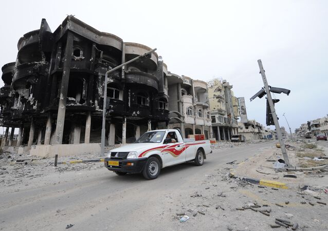 This file photo taken on October 24, 2011 shows Libyans driving through a destroyed neighbourhood in Sirte