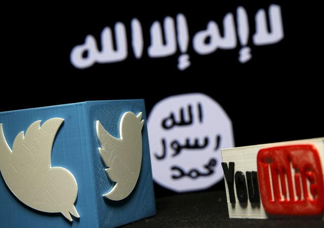 A 3D plastic representation of the Twitter and Youtube logo is seen in front of a displayed ISIS flag in this photo illustration in Zenica, Bosnia and Herzegovina, February 3, 2016