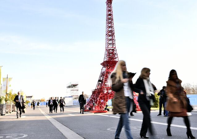 People pass by a miniature Eiffel Tower displayed at the COP21, the United Nations conference on climate at Le Bourget, on the outskirts of Paris on December 3, 2015.
