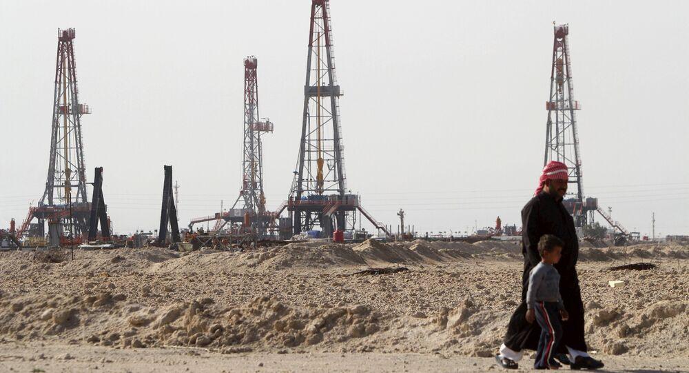 Iraqi people walk past the Rumaila oilfield in Basra, Iraq, January 26, 2016