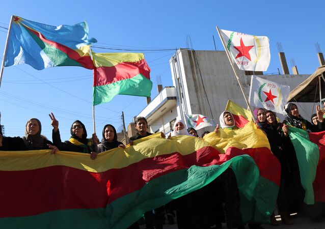 Kurdish women hold flags of the Kurdish People's Protection Units (YPG) political wing, the Democratic Union Party (PYD), and banners during a demonstration against the exclusion of Syrian-Kurds from the Geneva talks in the northeastern Syrian city of Qamishli on February 4, 2016