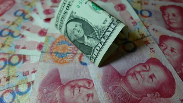Yuan banknotes and US dollars are seen on a table in Yichang, central China's Hubei province on August 14, 2015 - Sputnik International
