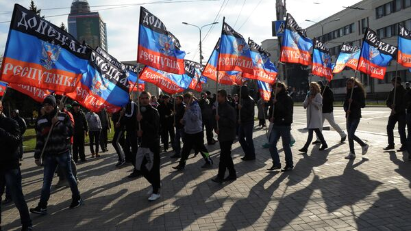 People carry flags of the self-proclaimed Donetsk People's Republic (DPR) during a ceremony for the presentation of the DPR flag at the Lenin square of Donetsk, on October 19, 2014 - Sputnik International