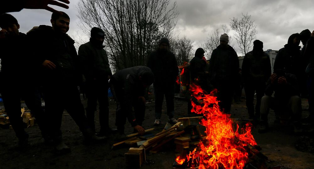 Migrants try to warm up around a brazier in a muddy field at a camp of makeshift shelters.