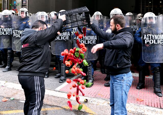 Farmers throw vegetables in front of the Agriculture ministry in Athens during a demonstration of farmers against the pension reform on February 12, 2016.