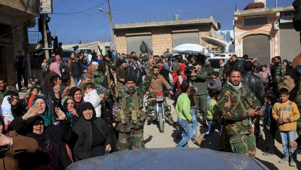 Residents of Nubul and al-Zahraa, along with forces loyal to Syria's President Bashar al-Assad, celebrate after the siege of their towns was broken, northern Aleppo countryside, Syria, in this handout picture provided by SANA on February 4, 2016 - Sputnik International