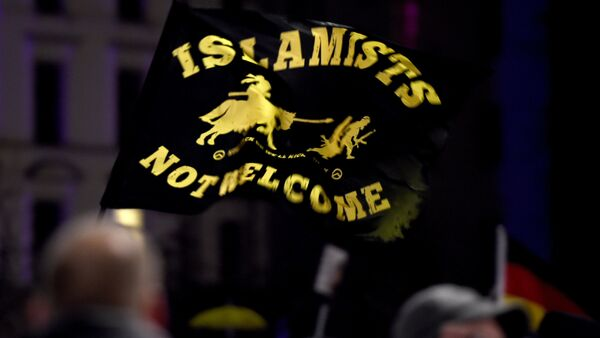 A flag reading Islamists not welcome flies among protestors from the PEGIDA movement (Patriotic Europeans Against the Islamisation of the Occident) attend a rally in Leipzig on January 11, 2016 - Sputnik International