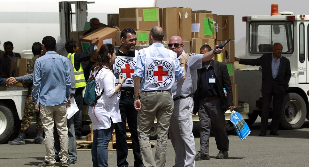 Workers from the International Committee of the Red Cross (ICRC) stand on the tarmac as emergency medical aid from the ICRC is offloaded off a plane following its arrival at the international airport in Sanaa on April 10, 2015