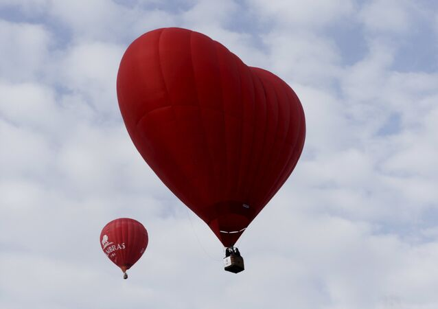 A heart-shaped hot air balloon (R) flies in the sky during the Love Cup 2016 event, ahead of Valentine's Day, in Jekabpils, Latvia, February 13, 2016