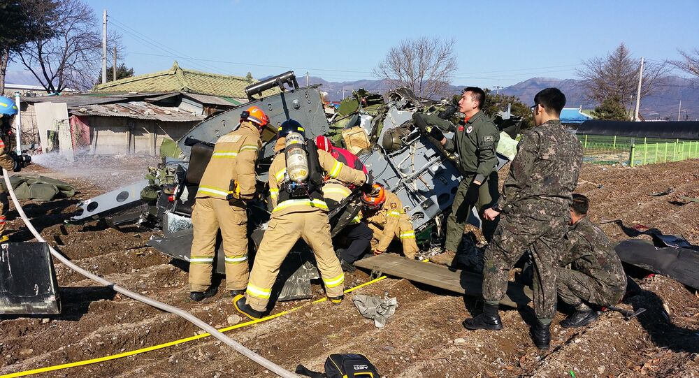 Rescue personnel stand before a crashed UH-1H military helicopter in a field in Chuncheon, in South Korea's eastern Gangwon province, on February 15, 2016.