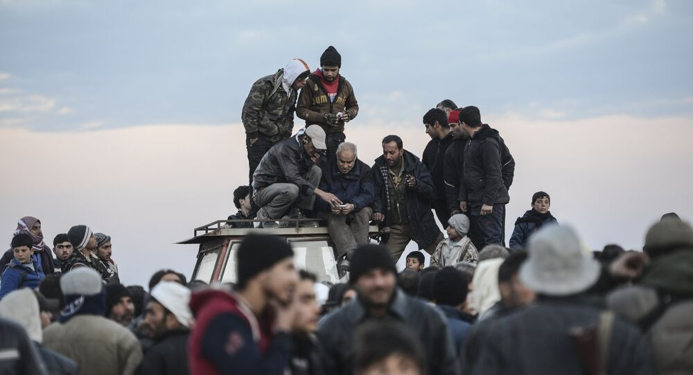 Men stand on a roof of a vehicle as Syrians fleeing the northern embattled city of Aleppo wait on February 5, 2016 in Bab-Al Salama, next to the city of Azaz, northern Syria, near Turkish crossing gate.