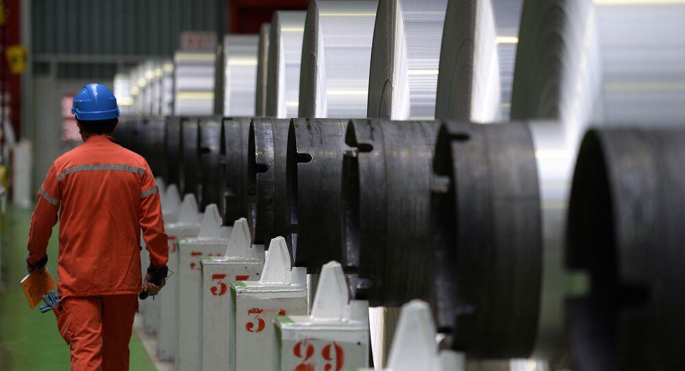 An employee walks along aluminium rolls at the Constellium factory, on December 12, 2014 in Biesheim, eastern France.