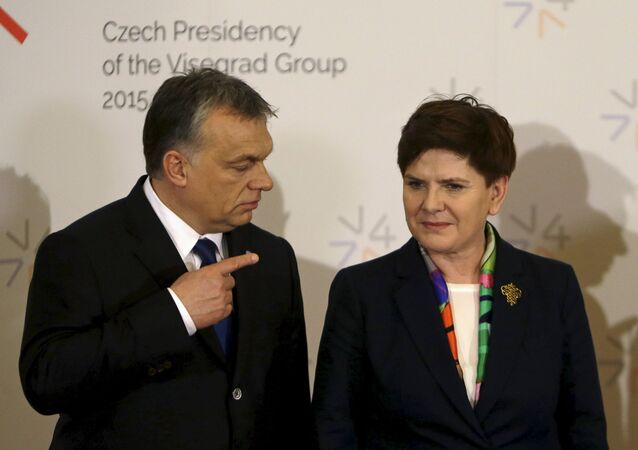 Hungary's Prime Minister Viktor Orban (L) points at Poland's Prime Minister Beata Szydlo during an extraordinary Visegrad Group summit aimed at resolving the migration crisis in Prague, Czech Republic, February 15, 2016.