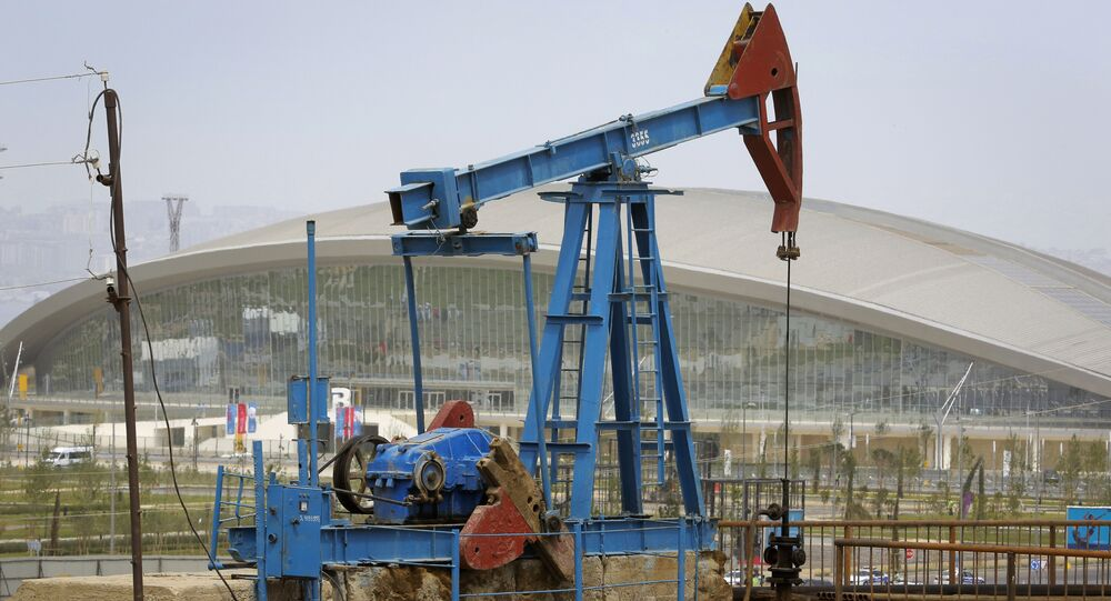 The Baku Aquatics Centre, one of the venues of the 2015 European Games stands in the background, as an oil pump works a nearby field in Baku, Azerbaijan.