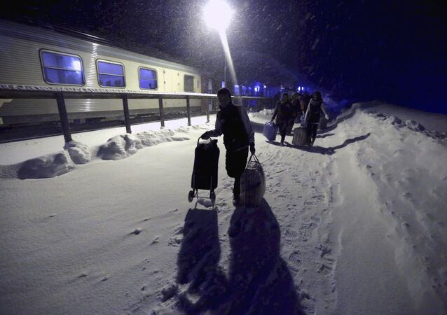 Refugees disembark and make their way to a camp at a hotel touted as the world's most northerly ski resort in Riksgransen, Sweden, in this December 15, 2015 file photo.