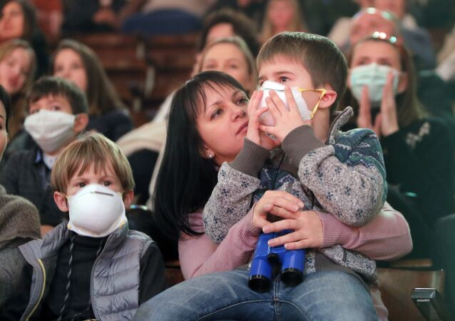 Children in face masks watch a performance at the circus, in the Ukrainian capital Kiev Thursday, Jan. 21, 2016