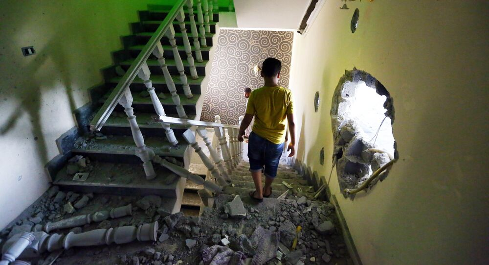 A youth walks down the stairs near a hole in the wall of a house at a former Libyan army camp known as Camp 27, in the Libyan capital Tripoli (File)