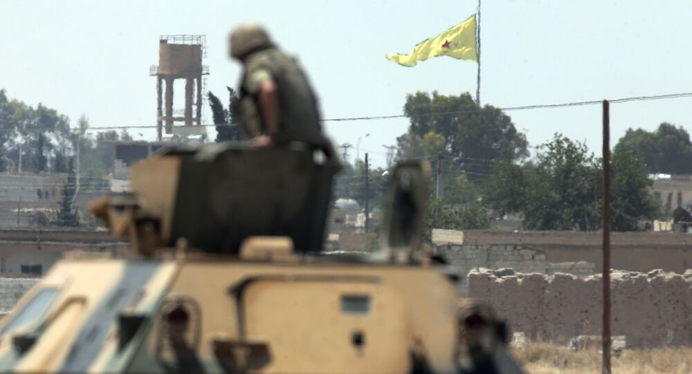 In this photo taken from the Turkish side of the border between Turkey and Syria, in Akcakale, southeastern Turkey, a Turkish soldier on an armoured personnel carrier watches as in the background a flag of the Kurdish People's Protection Units, or YPG, is raised over the city of Tal Abyad, Syria, Tuesday, June 16, 2015