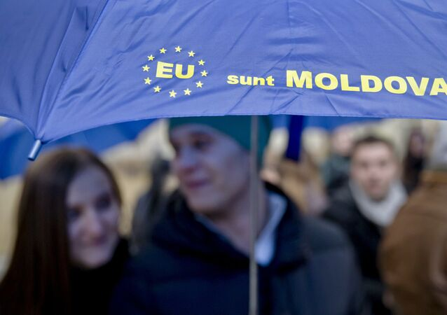 Moldovan students hold an umbrella that uses the European Union symbol to form the sentence I am Moldova after arriving in the Romanian capital to vote, at the main railway station, Gara de Nord, in Bucharest, Romania, Sunday, Nov. 30, 2014